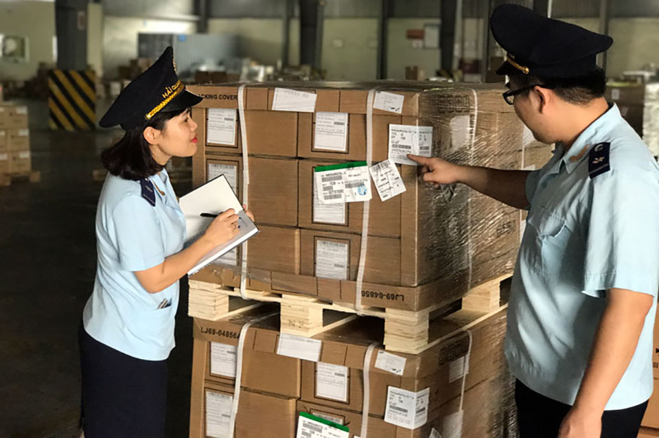 Customs officers carry out inspection of imported goods at customs clearance